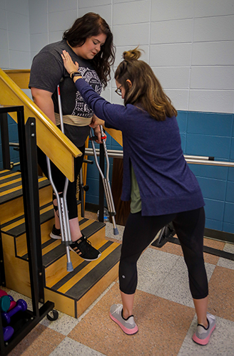 female in crutches walking down stairs with assistance
