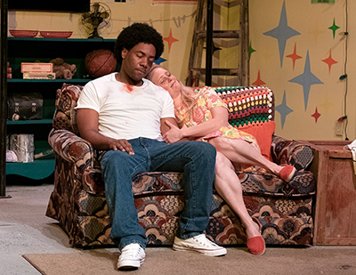 "scene from the play ""Detriot 67"" an afican american male and white female sitting on a sofa"