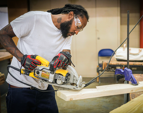 student using circular saw to cut wood