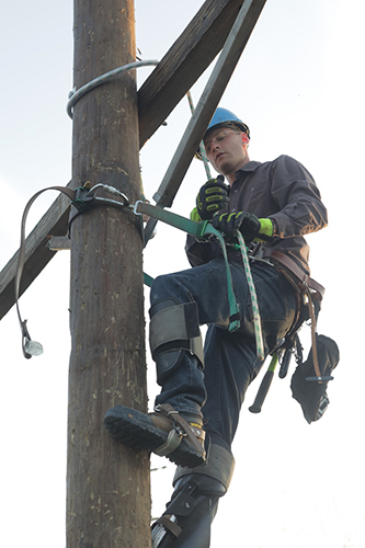 student on a pole setting up an electric line