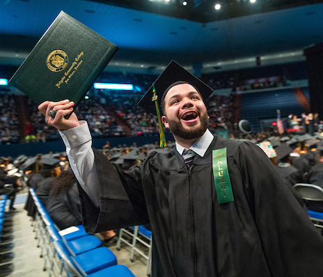male student graduating and holding up diploma