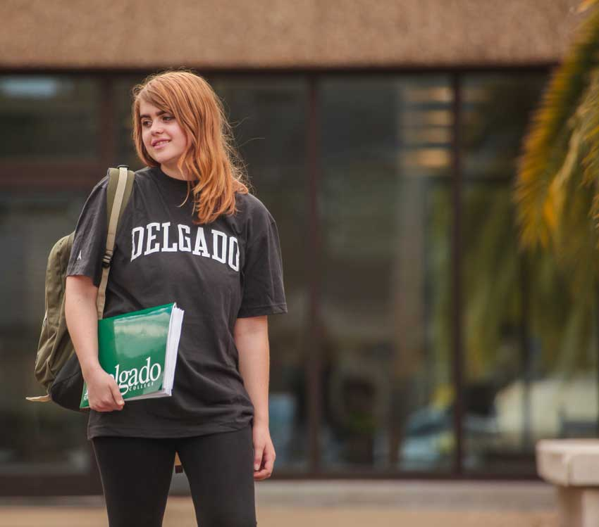 A young female Delgado student wearing a Delgado t-shirt poses in front of an academic building holding a Delgado branded folder and wearing a backpack.
