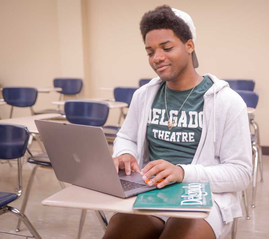 A Delgado theatre student uses his laptop in a classroom.