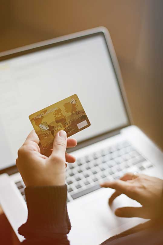 A woman makes an online payment via credit card.