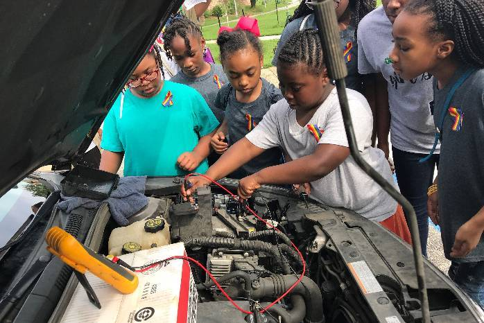 Girl Scouts work on a car