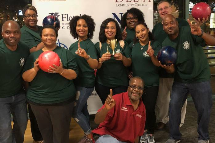 "Delgado faculty and staff pose for a photo after winning a trophy at the ""Bowling for a Cause"" event."