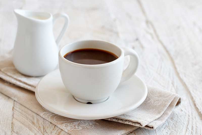 A cup of coffee rests on a white table cloth.