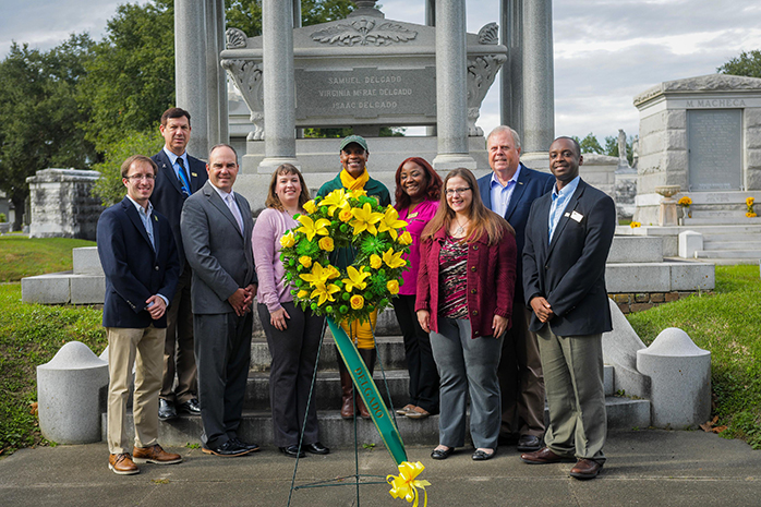 Delgado faculty and staff pose in front of Isaac Delgado's grave in celebration of Founder's Day.