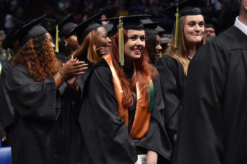 A Delgado graduate smiles during the Spring 2018 commencement ceremony