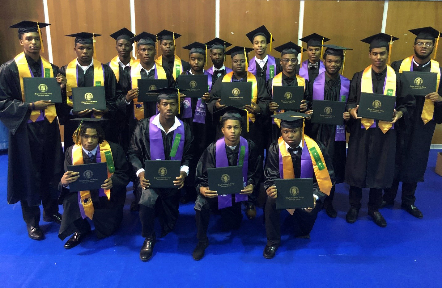 Warren Easton Charter High School students pose for a photo, holding their Delgado diplomas, after graudating from a Delgado dual enrollment program