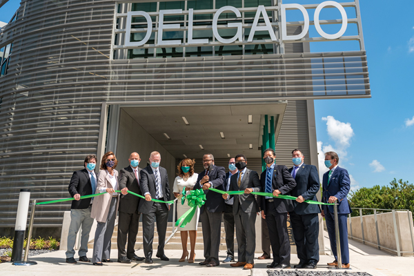 group photo of the ribbon cutting in front of the new building